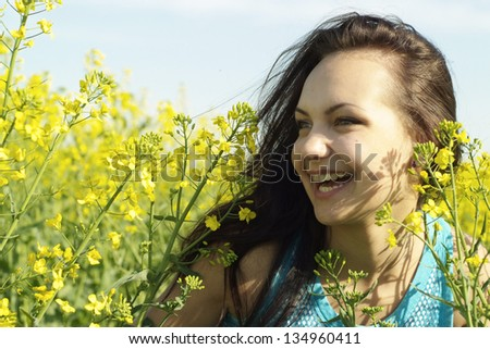Cute young girl in the middle of a field of yellow flowers #134960411