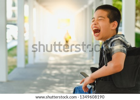 Asian special child on wheelchair is smile happily on ramp for disabled people background and orange light, Life in the education age of disabled children, Happy disabled kid concept. #1349608190