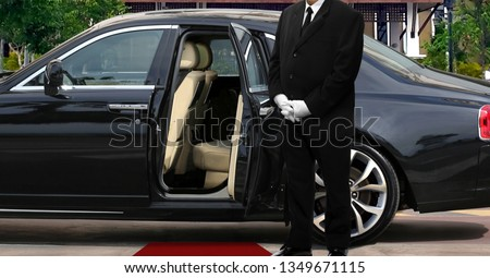 Limo driver standing next to opened car door with red carpet #1349671115