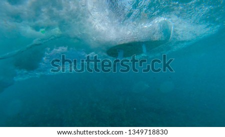 UNDERWATER: Unrecognizable surfer riding the glassy ocean waves on a new white surfboard. White surfboard gliding and carving through turquoise sea water and making ripples as it passes the camera. #1349718830