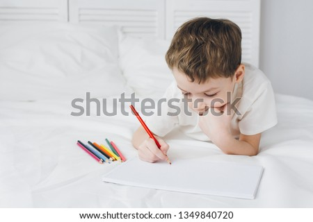 Cute boy draws with colorful pencils lying on the bed with white linens #1349840720