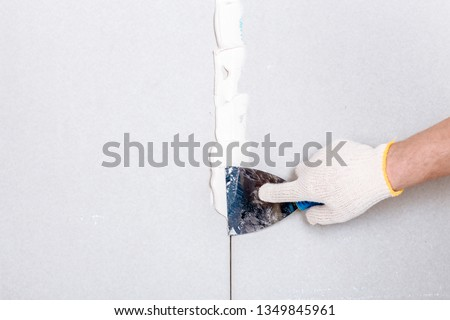 Man with putty knife shows how to hide the connection place between two pieces of dry walls using putty and construction tape #1349845961