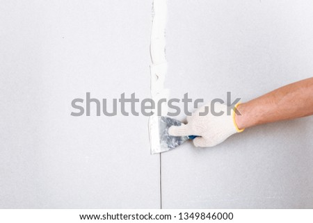 Man with putty knife shows how to hide the connection place between two pieces of dry walls using putty and construction tape #1349846000