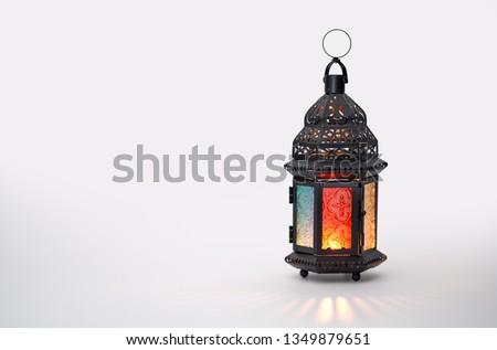 Ornamental Arabic lantern with burning candle glowing on white background. Festive greeting card, invitation for Muslim holy month Ramadan Kareem. #1349879651