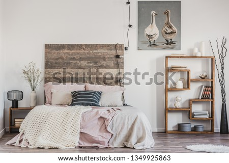 Cute poster with two ducks on white wall of tasteful bedroom interior with bed with pastel pink bedding #1349925863