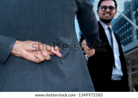 Politician shake hands together and holding another fingers crossed behind his back,Honesty isn't always,Here's when it might be better to lie,Dishonest businessman telling lies,Trickery Concept  Royalty-Free Stock Photo #1349972585