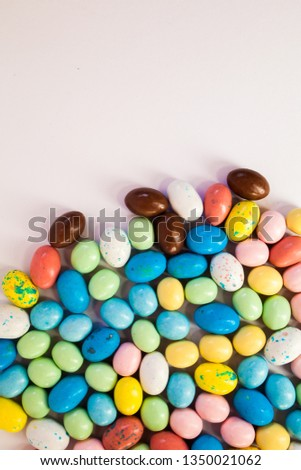 Multicolour sweet candies background with copyspace. Flat lay decoration for cake and bakery. Chocolate eggs for Easter treat. Holiday Concept. #1350021062