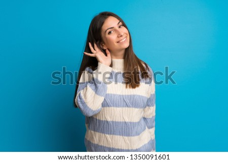 Young woman over blue wall listening to something by putting hand on the ear #1350091601