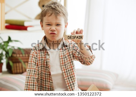 Wooden cubes with word despair in hands of little boy at home. Conceptual image about education, childhood and social problems. #1350122372