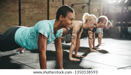 Smiling young African American woman in sportswear doing pushups during an exercise class with a group of friends at the gym Royalty-Free Stock Photo #1350138593