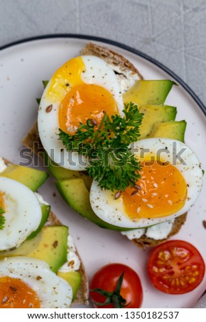Sandwich on grain bread with boiled egg and avocado on white plate, parsley, cherry tomatoes, avocado near on gray background. Macro concept of healthy food. Holiday Easter breakfast #1350182537