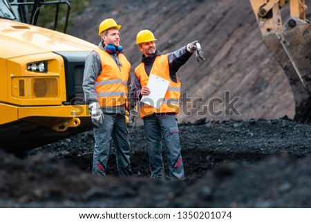 Worker with a plan and a clipboard discussing super important things in quarry #1350201074