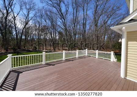 New backyard deck. White vinyl railings and composite brown boards. Large patio and garden space with a view to the woods. #1350277820