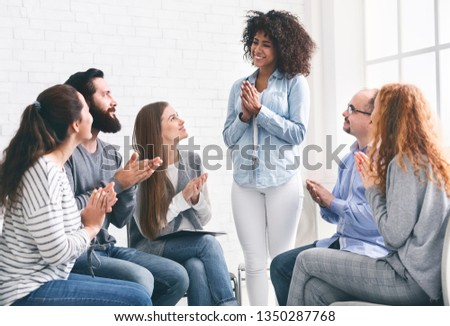 Young people clapping to black woman, supporting and cheering her up at rehab group meeting #1350287768