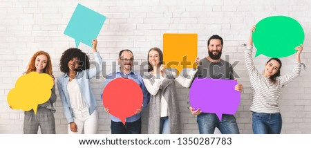 Global communications. Group of happy young diverse people holding empty colorful speech bubbles and smiling at camera #1350287783