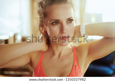 Portrait of dreamy active sports woman in sport clothes in the modern living room looking into the distance. #1350337982