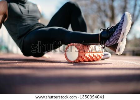 Man foam rolling. Athlete stretches using foam roller. #1350354041