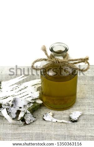 A decoction of birch bark. Birch bark on the table. A decoction of birch bark in the glass. #1350363116