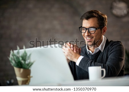 Happy businessman reading an e-mail while working on a computer in the office.  #1350370970