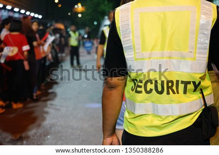 K-Pop music theme security guard with blurred crowd of audience or diversity people at concert venue entrance. Enjoy Music and Entertainment Concept. (selective focus, space for text, article layout) #1350388286