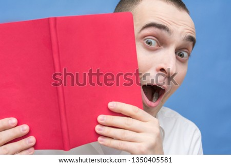 Man is shocked after reading the book,  looks out from behind an open book, cover of the red book, close up, background, copy space, for advertising, slogan