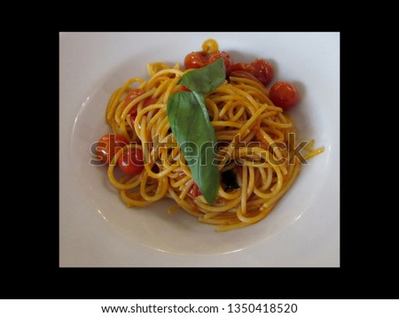 A fresh plate of past with tomato sauce and cherry tomatoes garnished with basil.            #1350418520