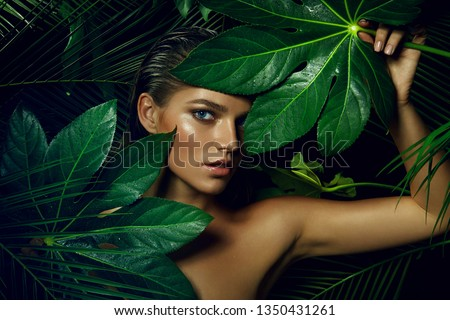 A beautiful tanned girl with natural make-up and wet hair stands in the jungle among exotic plants.fashion, beauty, health, ecology, makeup, personal care, hair, nature. #1350431261