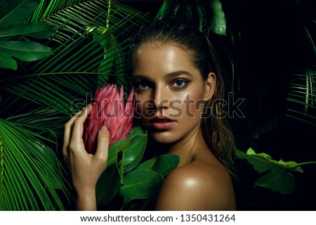A beautiful tanned girl with natural make-up and wet hair stands in the jungle among exotic plants.fashion, beauty, health, ecology, makeup, personal care, hair, nature. #1350431264