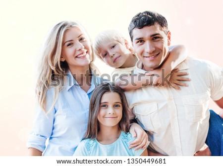 Beautiful smiling family sitting at sofa at home #1350449681