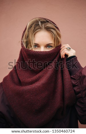 Photo of young blonde woman with closed scarf face on background of wall.
