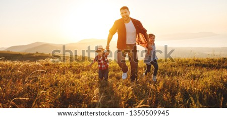 happy family father and children running in nature at sunset #1350509945