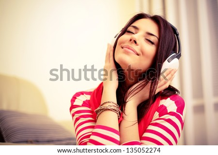Young beautiful woman in bright outfit enjoying the music at home Royalty-Free Stock Photo #135052274
