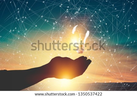 Abstract science. Hand holding brain digital network and light bulb inside on networking connection in city background. Idea and imagination. Creative and inspiration. Innovative technology #1350537422