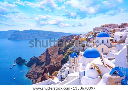 Beautiful Oia town on Santorini island, Greece. Traditional white architecture  and greek orthodox churches with blue domes over the Caldera, Aegean sea. Scenic travel background. #1350670097