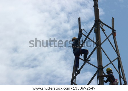 sidoarjo, east java-indonesia. Tuesday, March 26, 2019. Unloading electricity poles #1350692549
