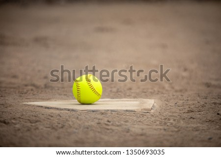 Neon softball on home plate with infield dirt in the background, in a sports background