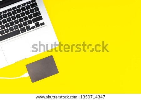 Laptop keyboard, storage drive or hard disk on yellow background with selective focus and crop fragment. Business, backup and copy space concept. #1350714347