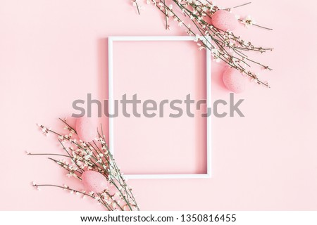 Easter composition. Easter eggs, photo frame, white flowers on pastel pink background. Flat lay, top view, copy space.