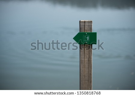 A pictogram with an angel symbol before a lake #1350818768