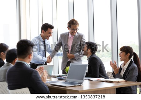 Handshake between the foreign CEO and the Asian manager who can successfully complete the project which makes the company gain profit from the annual sales top ranking in the region #1350837218