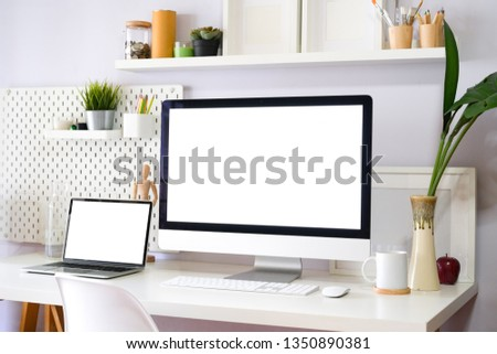 Stylish loft workspace with desktop computer and office supplies #1350890381
