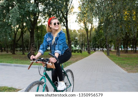 Stylish, happy girl in stylish clothes and sunglasses rides a bike in the park, looks sideways and smiles. Walk on the bike in the park. Active in the rest of the concept. #1350956579