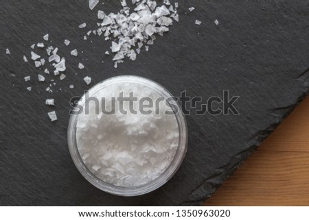 Salt in a container with salt flake crystals on black slate background on wooden table - Top view photo #1350963020