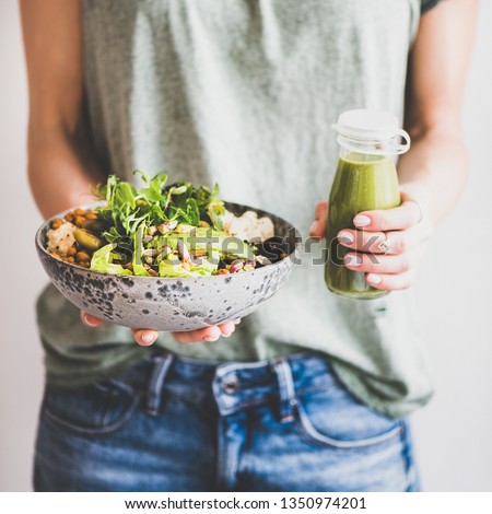 Healthy dinner or lunch. Woman in t-shirt and jeans standing and holding vegan superbowl or Buddha bowl with hummus, vegetable, salad, beans, couscous and avocado and smoothie in hands, square crop #1350974201
