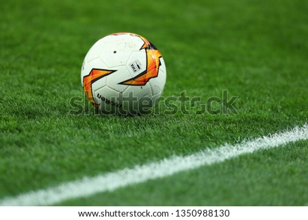 KYIV, UKRAINE - MARCH 14, 2019: Molten football ball on. Official Match Ball of the UEFA Europa League close-up view. Isolated green grass background. Europa League. #1350988130