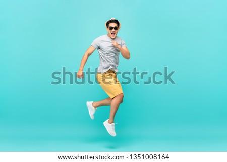 Amazed handsome Asian tourist man jumping studio shot isolated on light blue background #1351008164