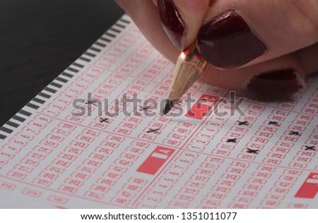 woman Hand Playing Turkish Lottery .(Turkish Sayisal Loto, Super loto, Sans topu, on numara game) #1351011077