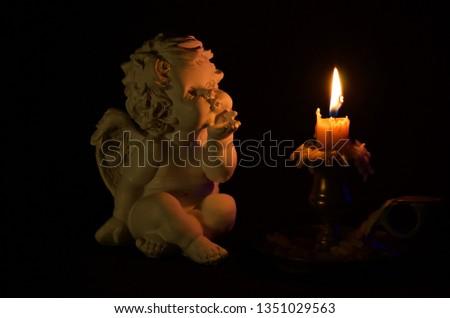 Angel figure and burning candle on black background. #1351029563