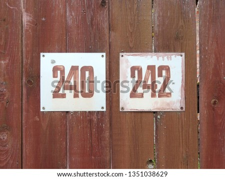 Two white plates with numbers two hundred forty and two hundred forty-two on the background of a wooden fence. #1351038629