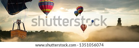 Beautiful panoramic nature landscape of countryside mountains with colorful high hot air balloons festival in summer sky. Vacation travel panorama background. #1351056074